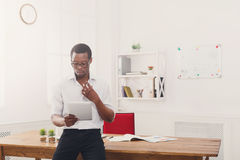 Skoncentrowany czarny biznesmen w nowożytnym biurze, praca z pastylką obrazy royalty free
