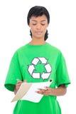 Skoncentrowany czarny z włosami ekologa writing na notatniku zdjęcia royalty free