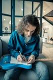 Skoncentrowany Długowłosy mężczyzny kładzenia notatnik na jego jaskrawej gitarze obraz royalty free