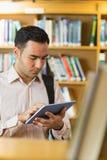 Skoncentrowany dojrzały studencki używa pastylka pecet w bibliotece zdjęcia stock