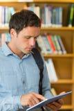Skoncentrowany dojrzały studencki używa pastylka pecet w bibliotece fotografia royalty free