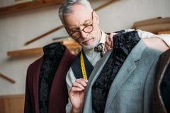 skoncentrowany dorośleć krawczyny z pomiarową taśmą egzamininuje kurtkę na mannequin fotografia stock