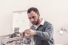 Skoncentrowany dorosły poważny specjalista konfiguruje 3D drukarkę fotografia royalty free