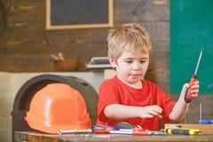 Skoncentrowany dzieciak bawić się z śrubokrętem Śliczny blond chłopiec uczenie pracować z narzędziami Mały repairman chwyta śrubę zdjęcia royalty free