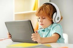Skoncentrowany dzieciak bawić się z cyfrową pastylką zdjęcia royalty free