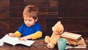 Skoncentrowany dzieciaka writing w copybook Preschool chłopiec obsiadanie przy biurkiem Uczyć się listy w dziecinu obraz royalty free