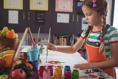 Skoncentrowany dziewczyna obraz przy biurkiem fotografia stock