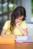 Skoncentrowany dziewczyny studiowanie podczas gdy siedzący przy biurkiem zdjęcie royalty free