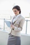 Skoncentrowany elegancki brown z włosami bizneswoman używa pastylka komputer osobistego obraz royalty free