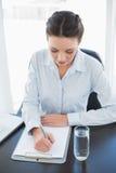 Skoncentrowany elegancki brunetka bizneswoman bierze notatki na schowku zdjęcie royalty free