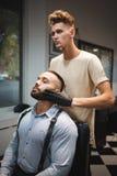 Skoncentrowany fryzjer projektuje brodę Klient i fryzjer męski w fryzjera męskiego sklepie na zamazanym tle Golenia pojęcie Zdjęcia Stock