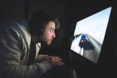 Skoncentrowany gamer siedzi przy monitorem i bawić się gry komputerowe obraz royalty free