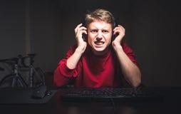 Skoncentrowany gniewny gamer bawić się gry na komputerze w domu zdjęcia stock
