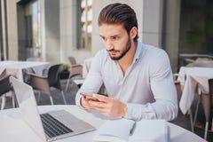 Skoncentrowany i spokojny młody człowiek siedzi attable i spojrzenia przy laptopu ekranem Trzyma telefon w rękach Tam otwiera zdjęcie stock