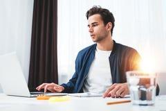 Skoncentrowany kierownik pracuje na laptopie i czytelniczej informacji w nowożytnym spale biurze obrazy stock