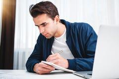 Skoncentrowany kierownik pracuje na laptopie i czytelniczej informacji w nowożytnym spale biurze zdjęcie stock