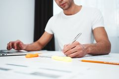 Skoncentrowany kierownik pracuje na laptopie i czytelniczej informacji w nowożytnym spale biurze obrazy royalty free