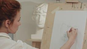 Skoncentrowany kobieta artysty obrazu tynku popiersie w sztuki studiu obraz stock