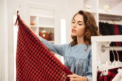 Skoncentrowany kobieta kupujący w błękita smokingowy wybierać odziewa fotografia royalty free
