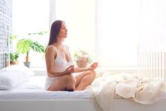 Skoncentrowany kobieta w ciąży medytuje w sypialni zdjęcie stock