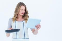Skoncentrowany kobiety mienie smaży niecki i pastylki komputer osobistego obraz stock