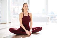 Skoncentrowany kobiety rozciąganie i robić joga w studiu obraz stock