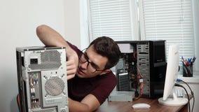 Skoncentrowany komputerowej usługa pracownik naprawia łamanego komputer w biurze i ulepsza komputerowego narzędzia poparcie zbiory wideo