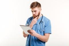 Skoncentrowany lekarki lub pielęgniarki główkowanie podczas gdy patrzejący pastylka komputer zdjęcia stock