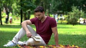 Skoncentrowany mężczyzna czyta detektywistycznej opowieści obsiadanie na szkockiej kracie w parku, podniecająca książka obraz stock