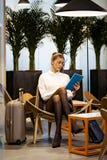 Skoncentrowany młody bizneswoman pracuje z jej cyfrowym pastylki obsiadaniem w hotelowym lobby zdjęcie royalty free