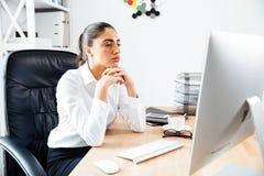 Skoncentrowany mądrze bizneswoman patrzeje ekran komputerowego zdjęcie stock