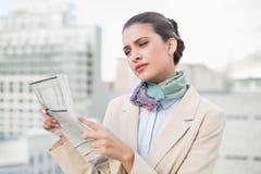 Skoncentrowany mądrze brown z włosami bizneswoman czyta gazetę zdjęcie royalty free