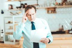 Skoncentrowany mężczyzna czyta list od partnerów biznesowych zdjęcie royalty free