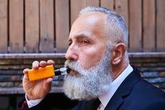 Skoncentrowany mężczyzna dymienia electrocigarette Fotografia Stock