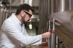 Skoncentrowany mężczyzna działanie jako piwowar zdjęcie royalty free