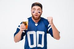 Skoncentrowany mężczyzna fan w błękitnej koszulce pije piwo fotografia royalty free