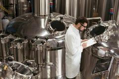 Skoncentrowany mężczyzna kontroluje mechanizmy przy piwną fabryką zdjęcia royalty free