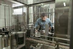 Skoncentrowany mężczyzna kontroluje produkty na browarnianej fabryce fotografia royalty free