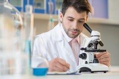 Skoncentrowany mężczyzna naukowiec pracuje z mikroskopem i bierze notatki obrazy stock