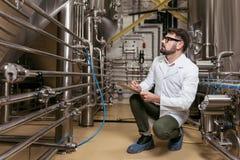 Skoncentrowany mężczyzna obsiadanie przy piwną fabryką zdjęcie royalty free