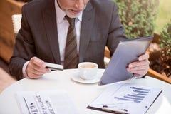 Skoncentrowany mężczyzna obsiadanie przy stołem fotografia royalty free
