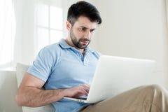 Skoncentrowany mężczyzna pisać na maszynie na laptopie w domu zdjęcie stock