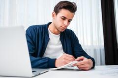 Skoncentrowany mężczyzna pisze nowych pomysłach w notepad patrzeje na parawanowym laptopie zdjęcia royalty free