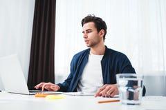 Skoncentrowany mężczyzna pisze nowych pomysłach w notepad patrzeje na parawanowym laptopie fotografia royalty free