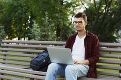 Skoncentrowany mężczyzna pracuje na jego laptopie outdoors obraz royalty free
