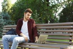 Skoncentrowany mężczyzna pracuje na jego laptopie outdoors zdjęcie royalty free