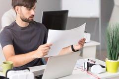 Skoncentrowany mężczyzna pracuje z papierami obraz stock