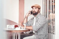 Skoncentrowany mężczyzna robi rozmowie telefoniczej podczas gdy siedzący w caffee obrazy stock