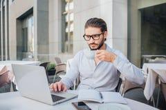 Skoncentrowany mężczyzna siedzi przy stołem i pracuje na laptopie Trzyma filiżankę herbata na ręce Tam jest otwierający notatnik  zdjęcia royalty free