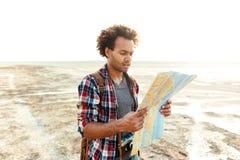Skoncentrowany mężczyzna stoi outdoors i rekonesansowa mapa fotografia royalty free